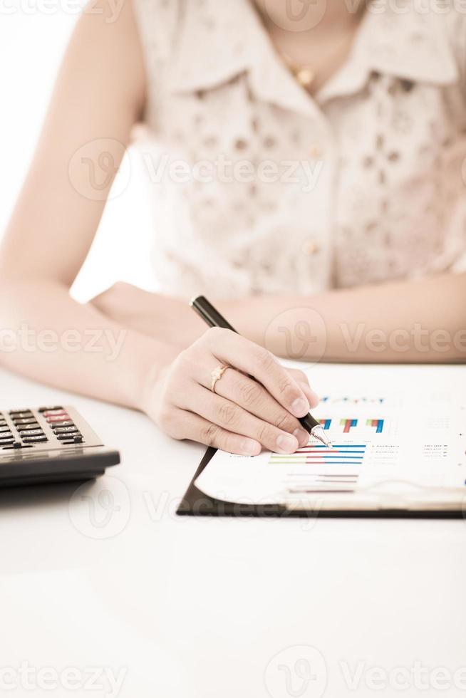 kvinnahand med penna och affärsrapport. bokföring foto