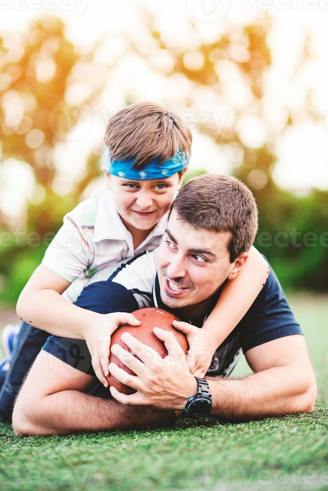 far och son som spelar fotboll i parken foto