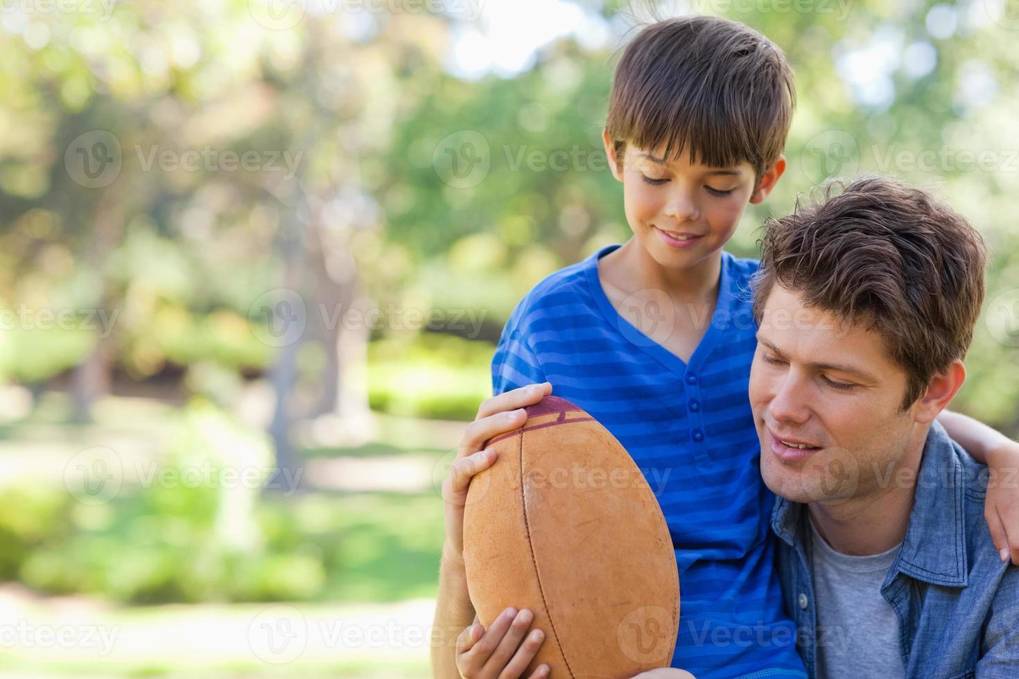 pojke och hans pappa tittar på fotbollen foto