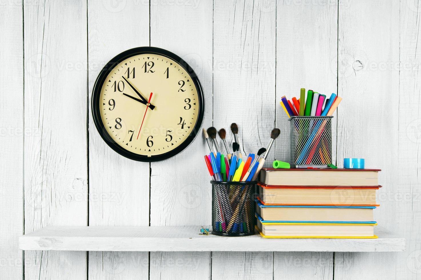 klockor, böcker och skolverktyg på trähylla. foto