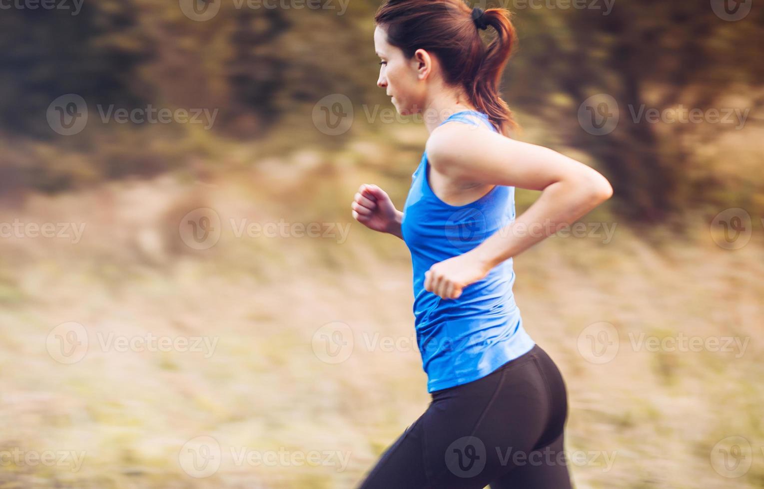 ung kvinna springer i naturen vid soluppgången foto
