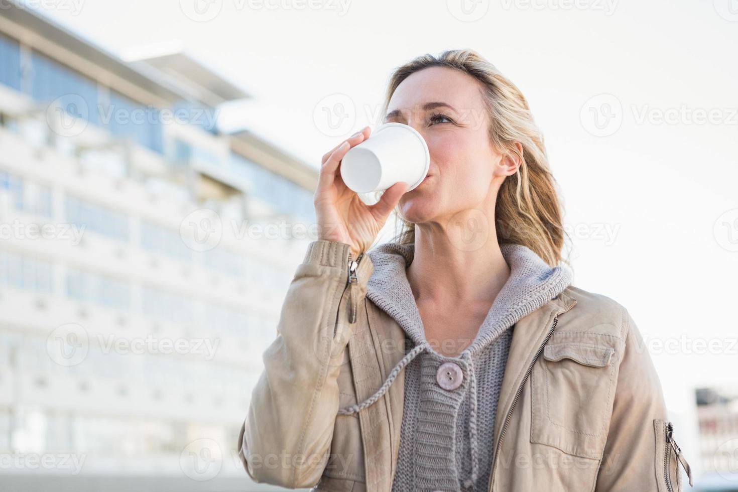 vacker blond dricka av engångskoppen foto