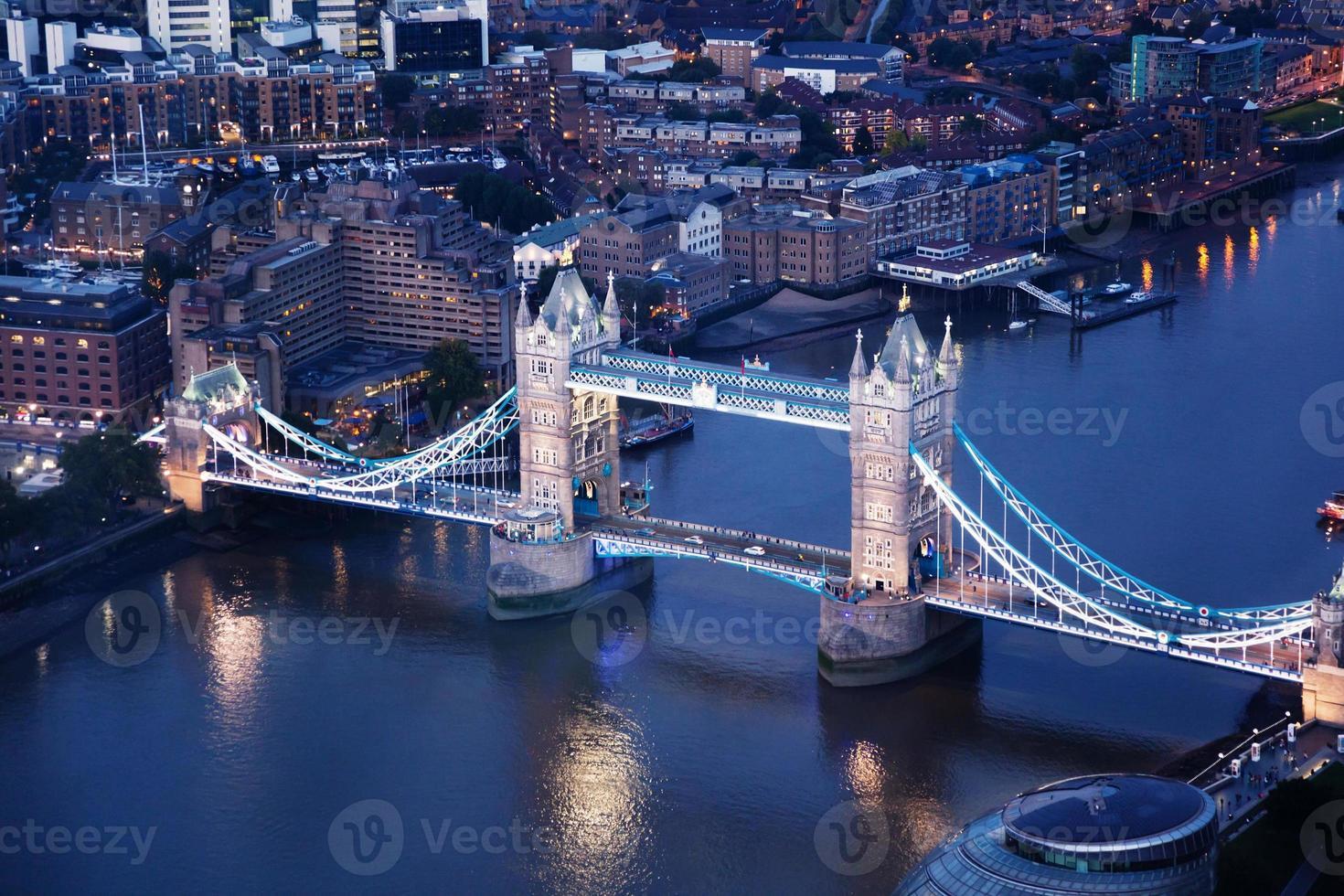 London på natten med stadsarkitekturer och tornbro foto