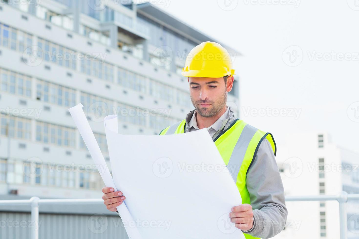 arkitekt som läser ritning utanför byggnaden foto
