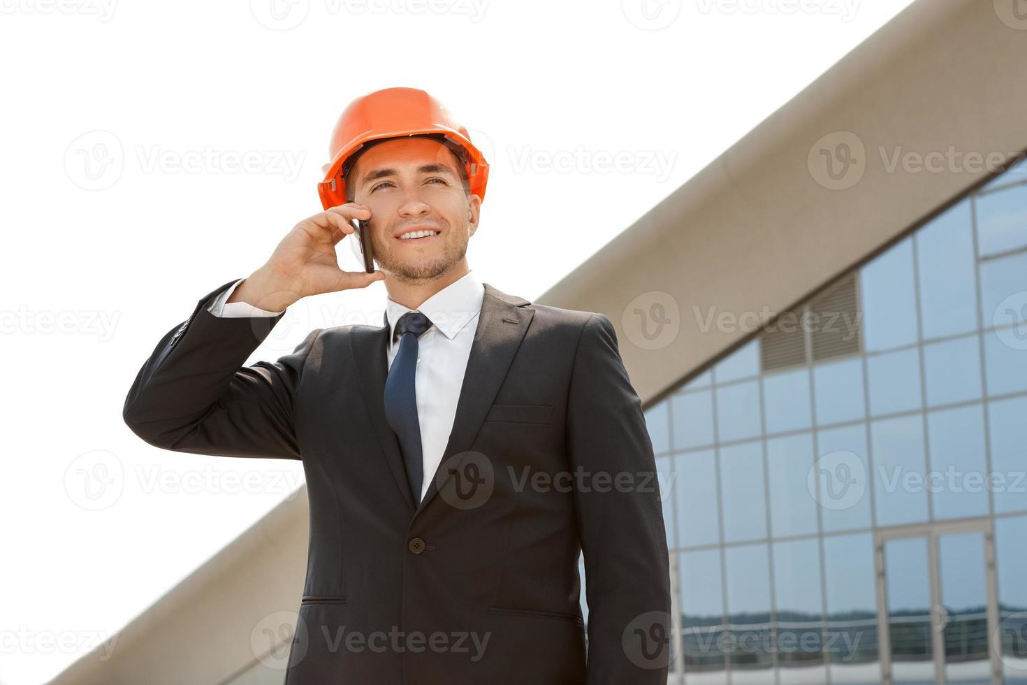 ung ingenjör som pratar i telefon foto
