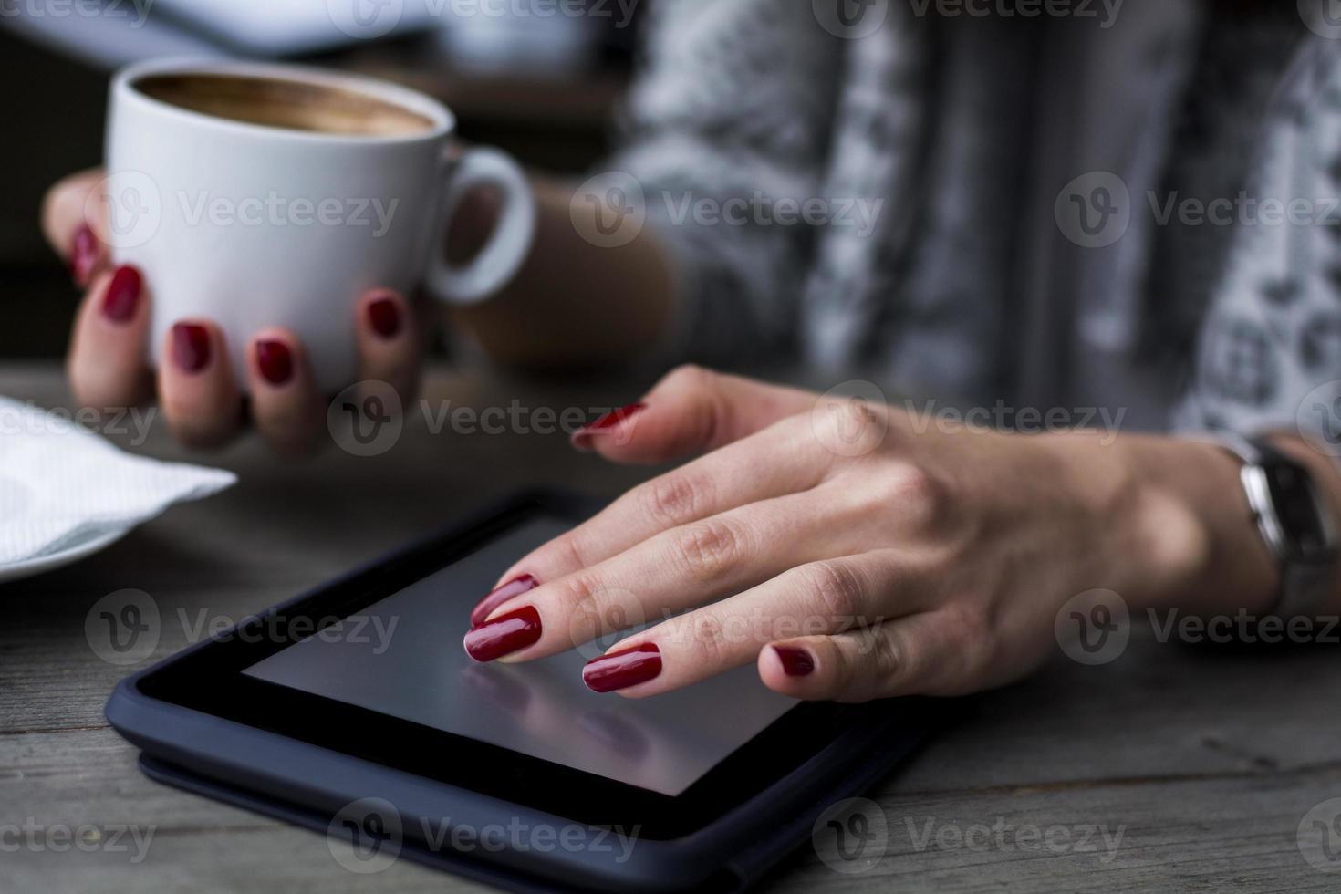 kvinnans hand som bläddrar på surfplattan foto