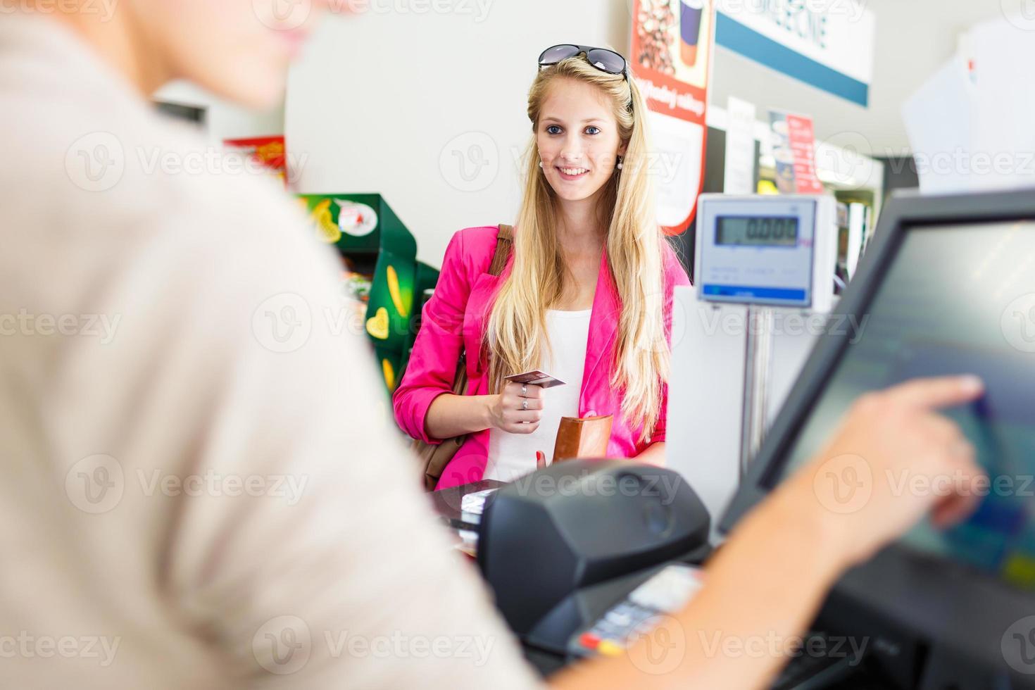 vacker ung kvinna som betalar för sina livsmedel foto