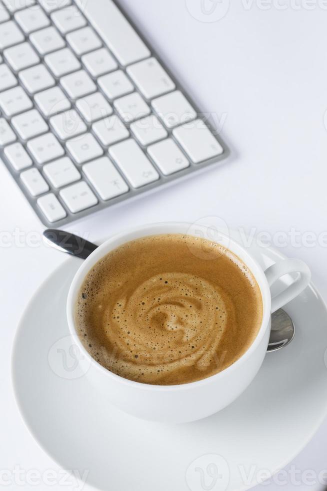 kopp kaffe med ett tangentbord foto