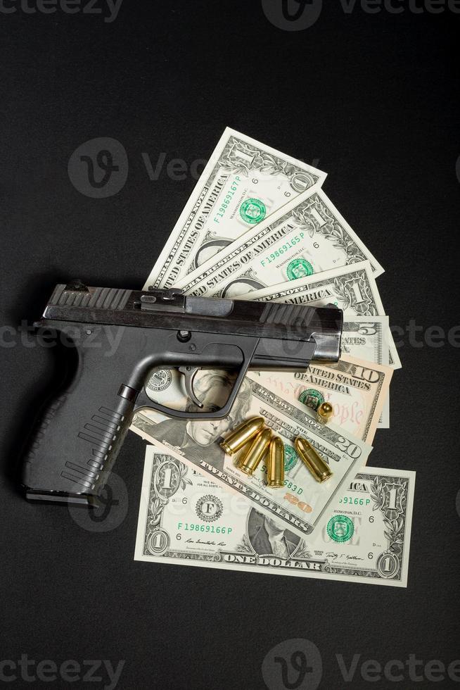 pistol med kula på oss dollarsedlar foto
