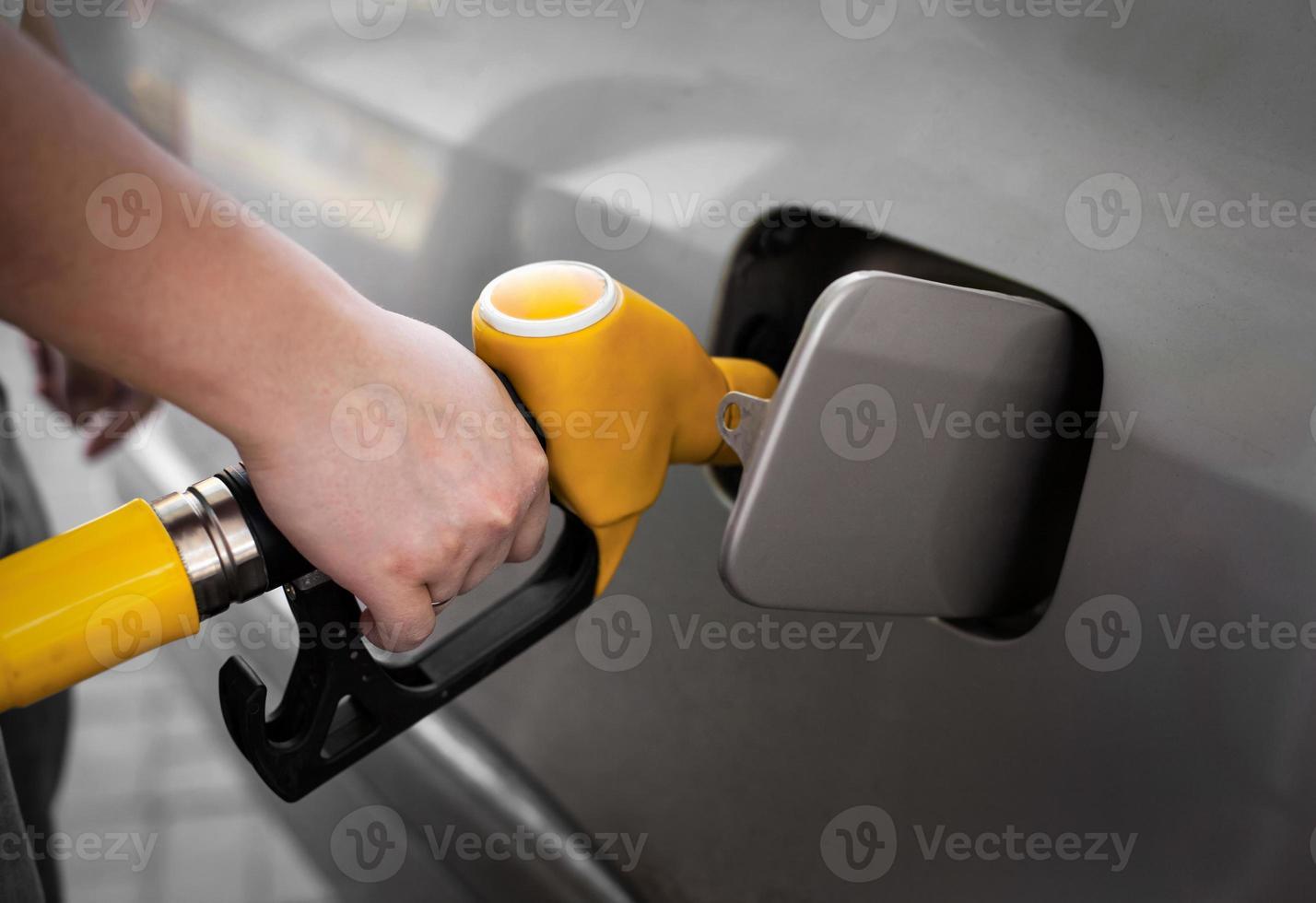 förare som pumpar bensin vid bensinstationen foto