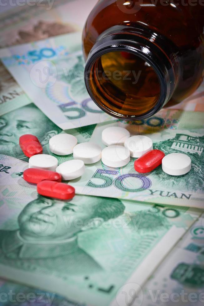 tabletter på yuan sedlar (renminbi) för medicineringskoncept. foto