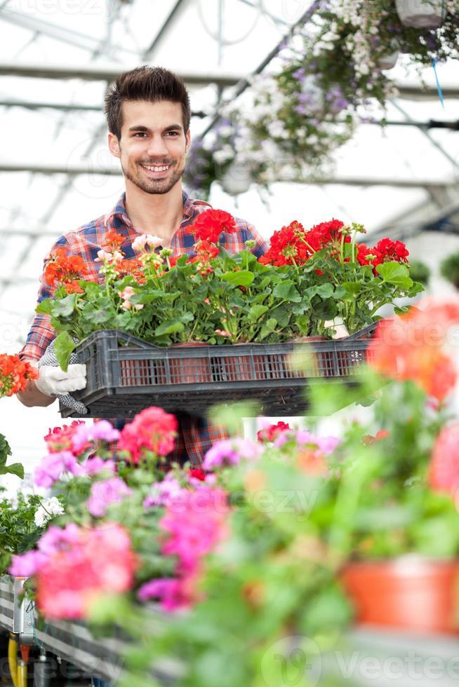 unga leende blomsterhandlare som arbetar i växthuset foto