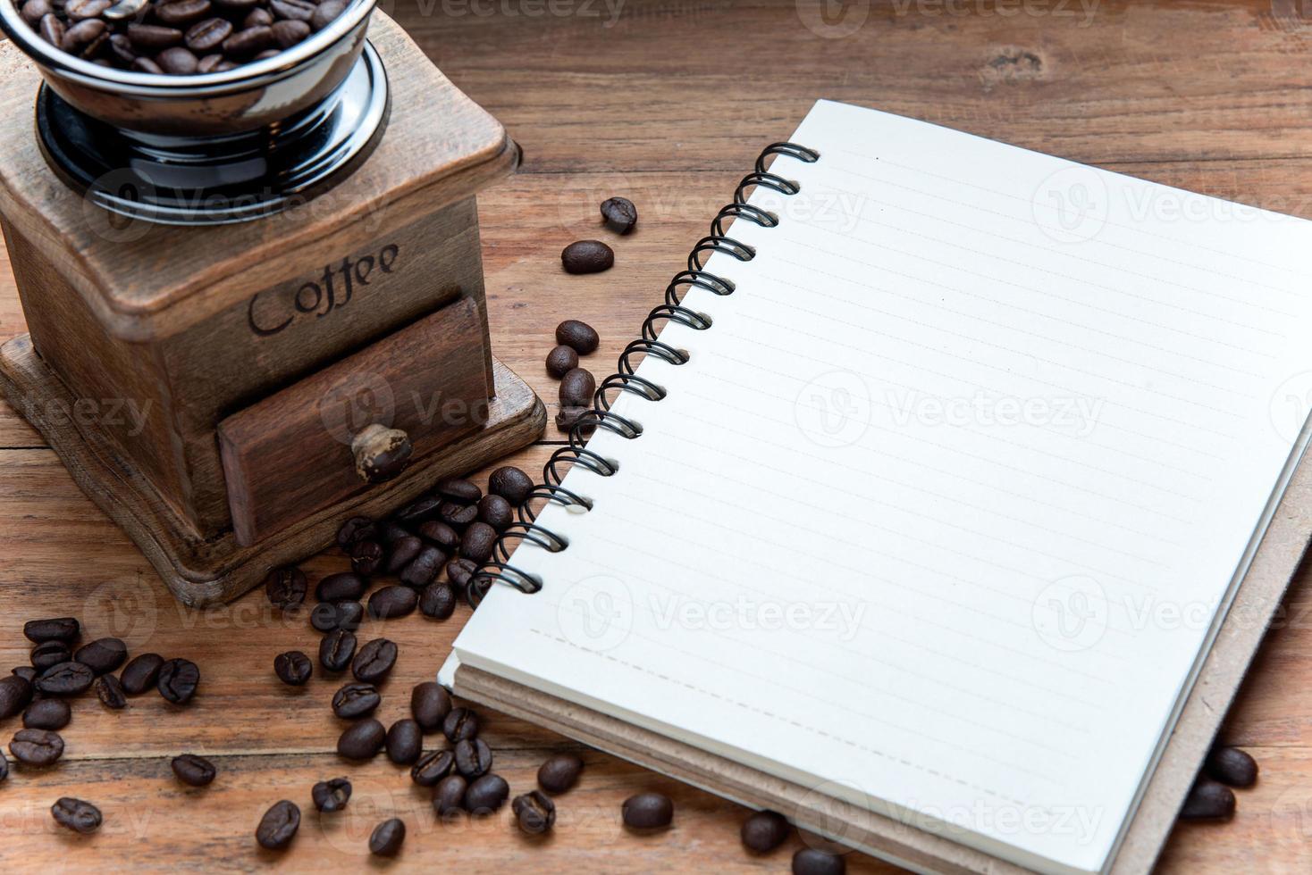 anteckningsbok med kaffebönor och kaffekvarn på träbord. foto