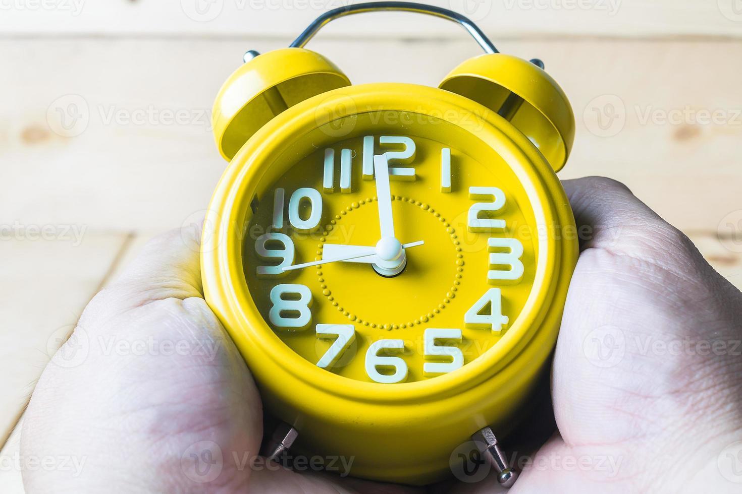 hand håller gul väckarklocka på trä bakgrund foto