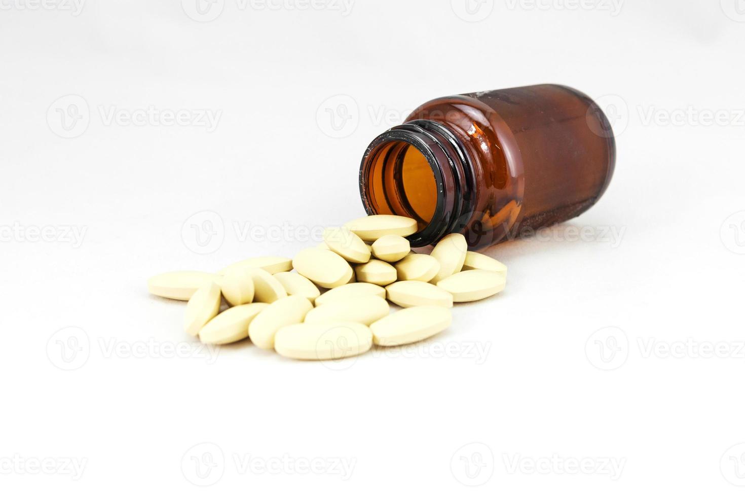 många tabletter med en glasflaska foto