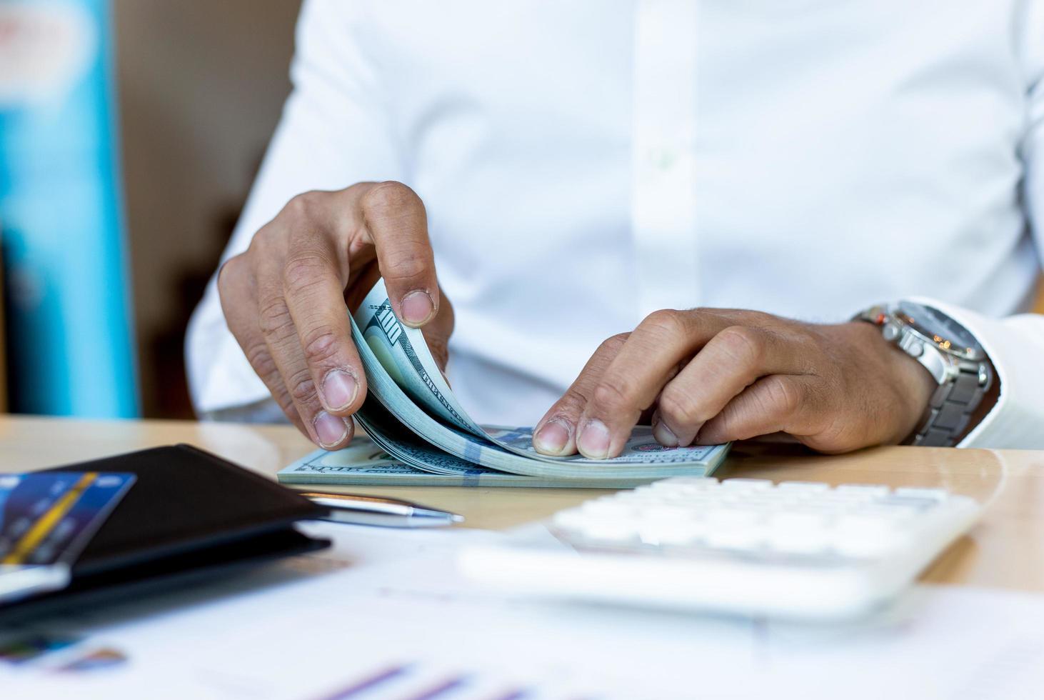 affärsman räknar pengar vid skrivbordet foto