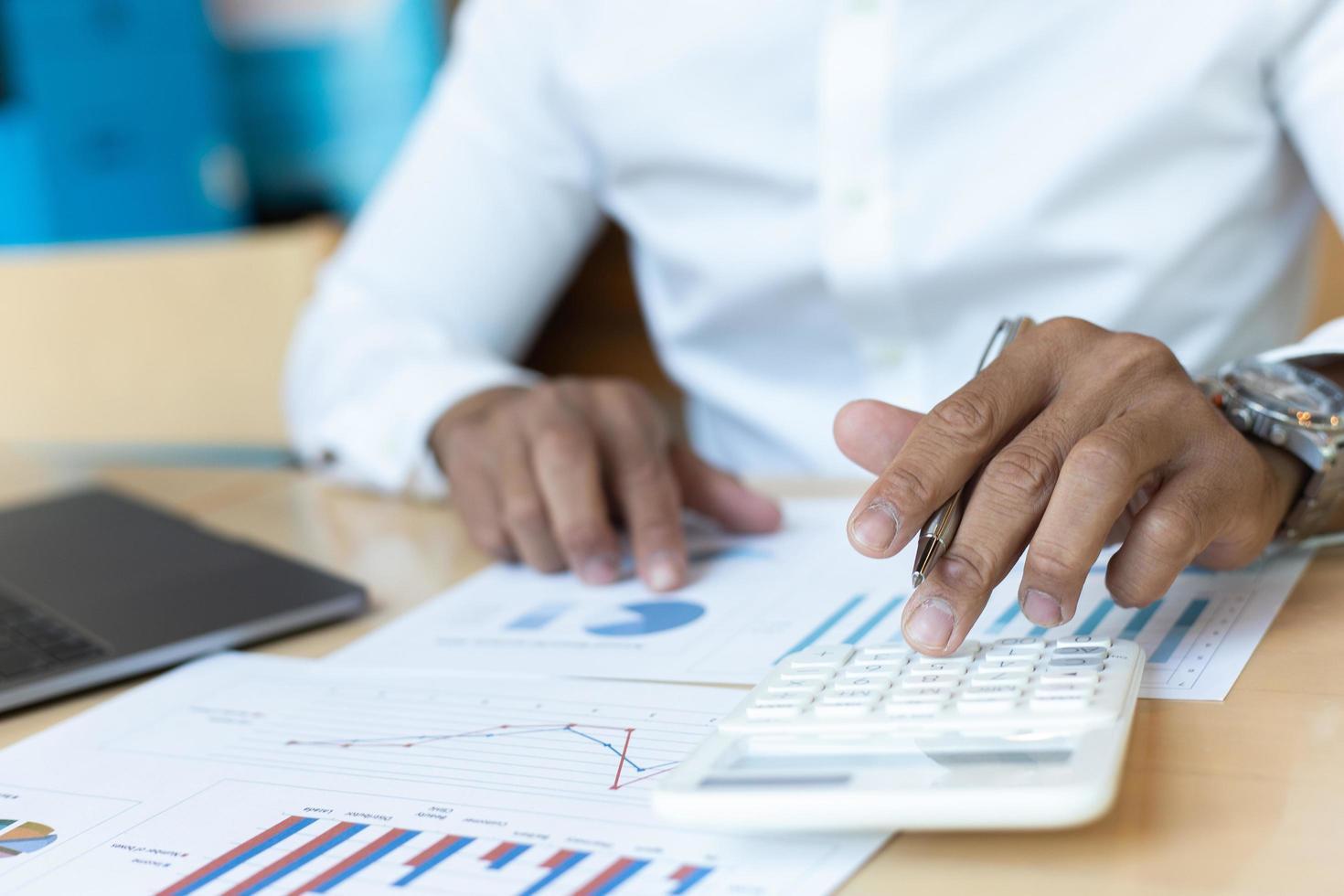 affärsman sitter vid skrivbordet analysera diagram med miniräknare foto