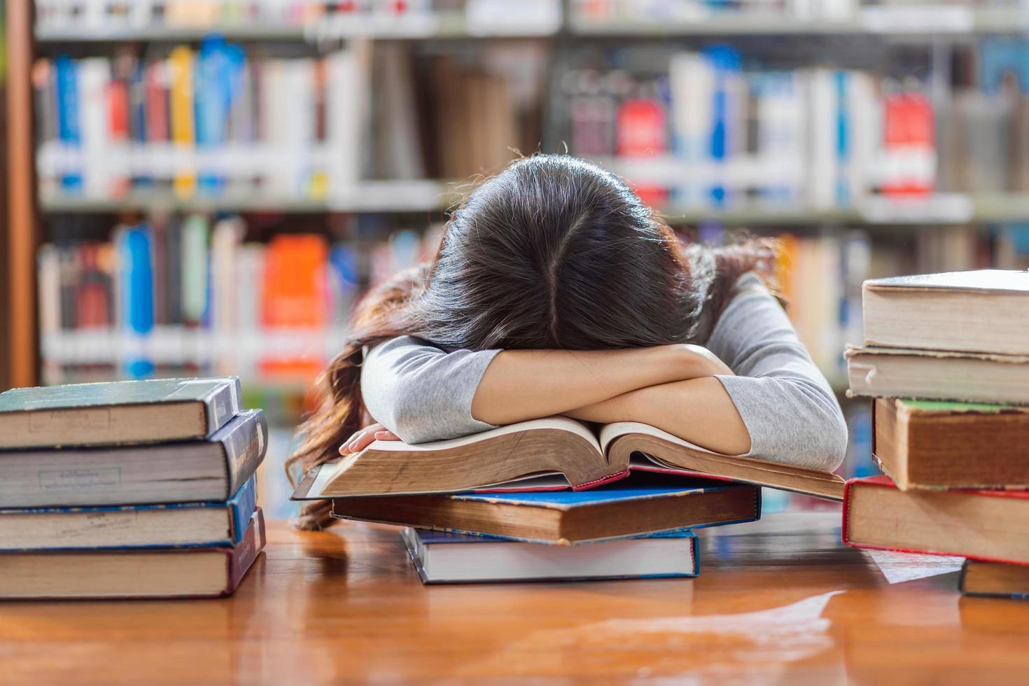 en ung student tar en studiepaus på ett bibliotek foto