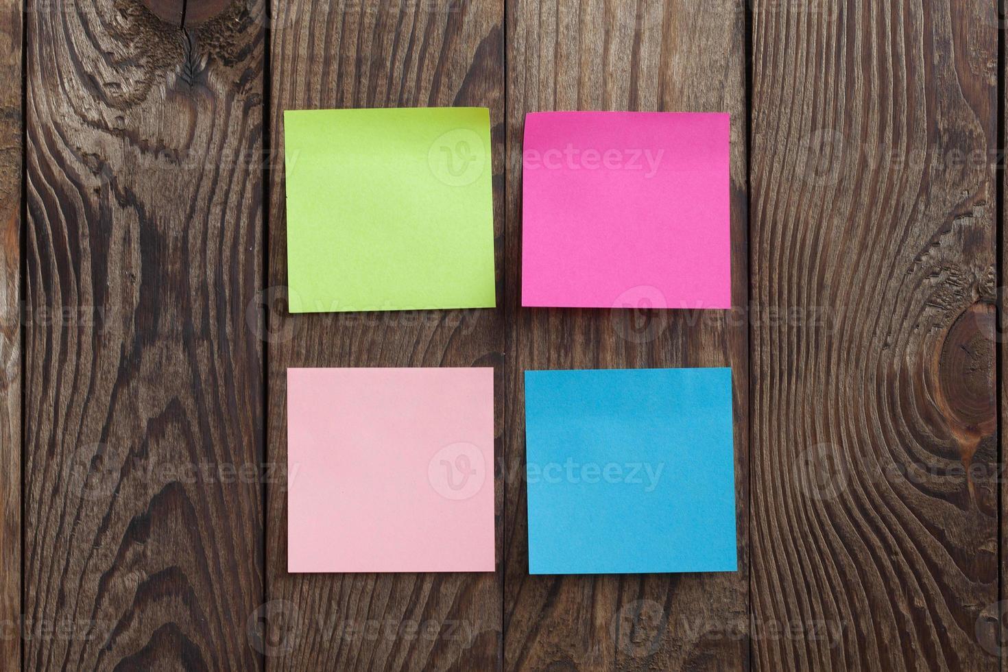 mångfärgade papper klistermärken anteckning på trä bakgrund foto