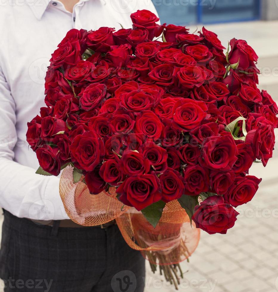 man i vit skjorta innehav bukett röda rosor foto