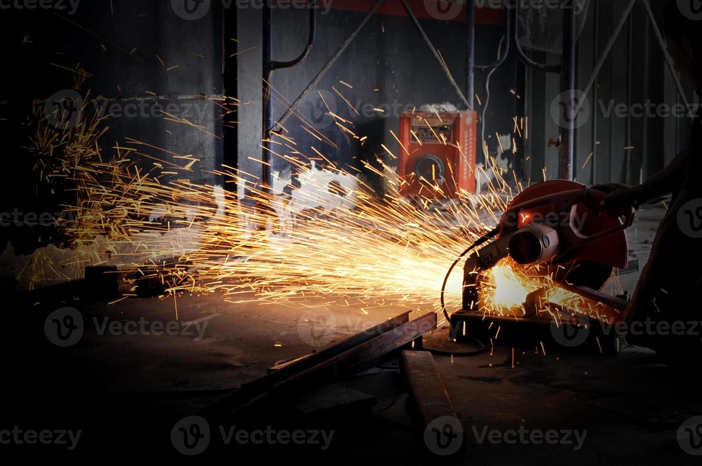 arbetare skärande metall med kvarn. gnistor under slipning av järn foto