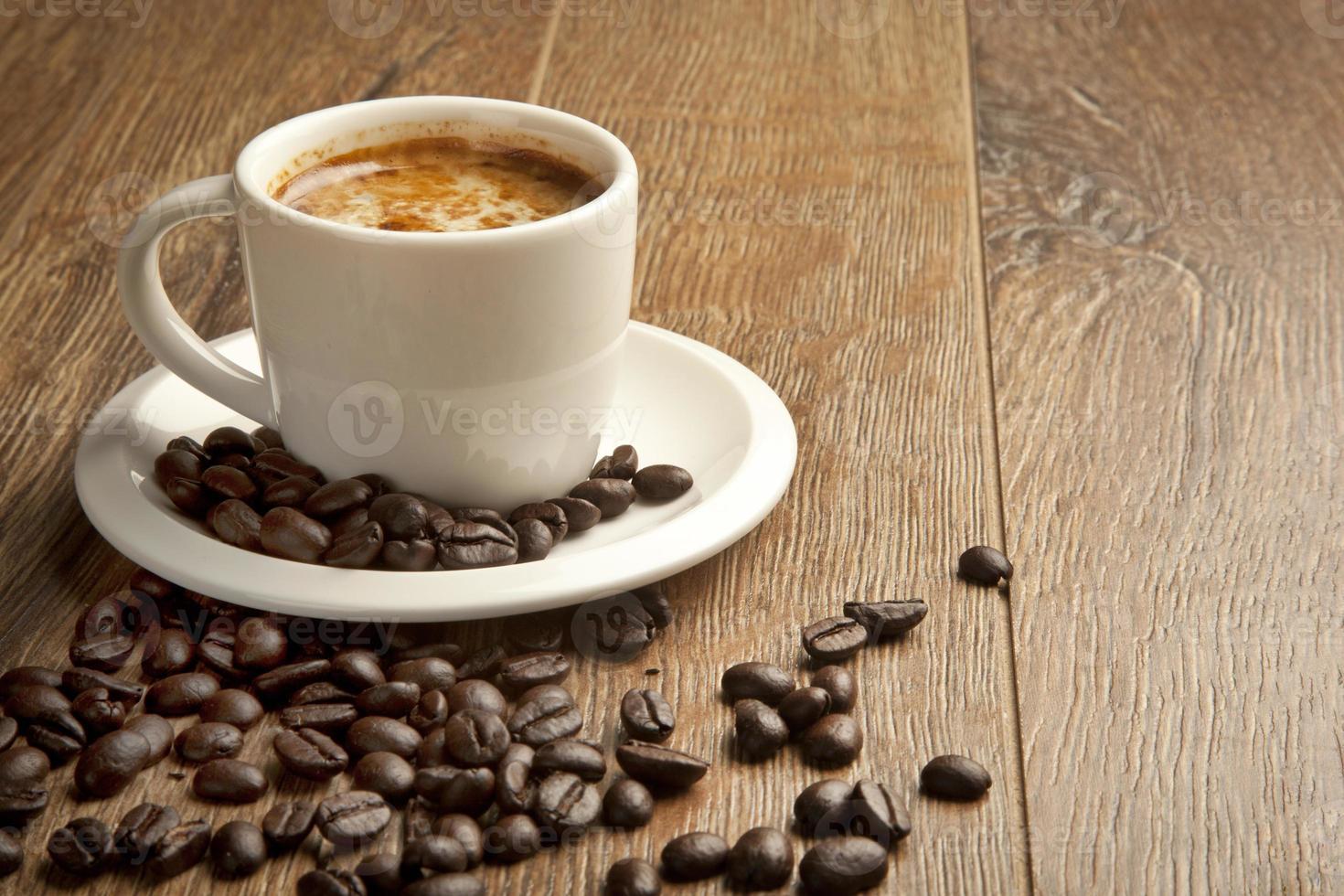 kaffekopp och fat på ett träbord foto