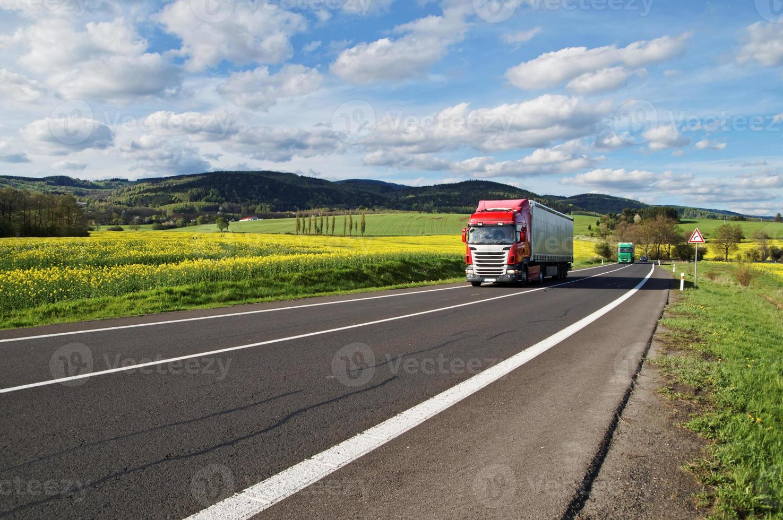 röda och gröna lastbilar på vägen mellan rapsfält foto