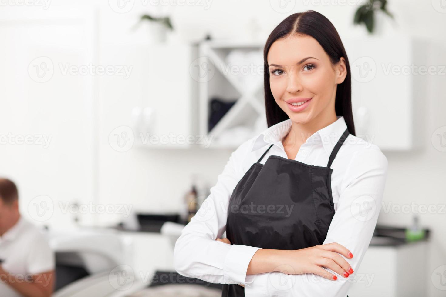 vacker ung kvinnlig frisör arbetar i salong foto