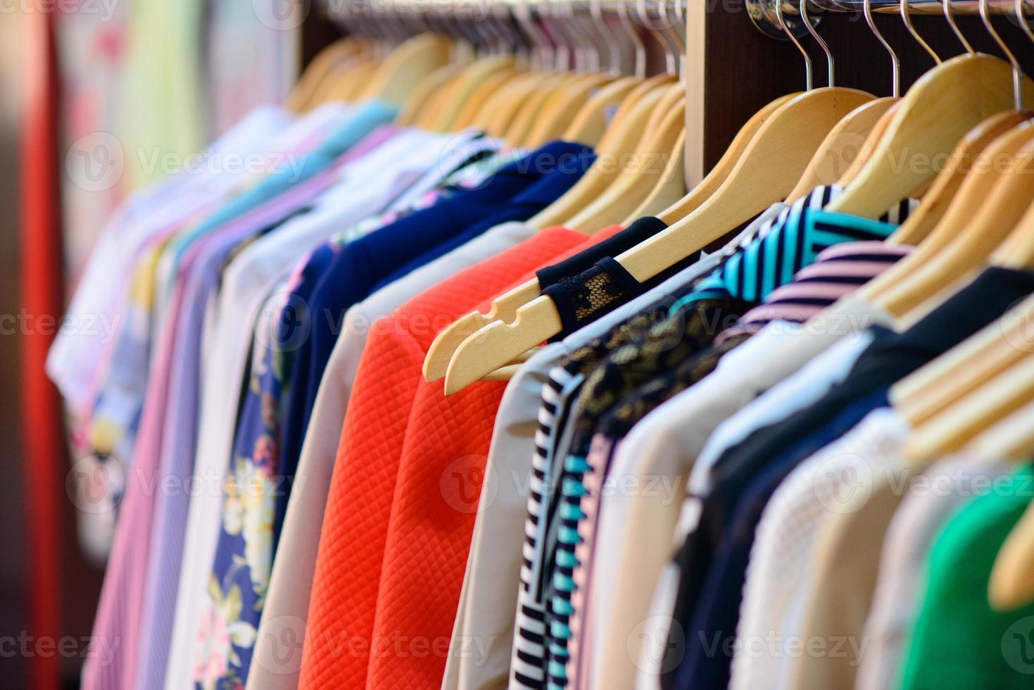olika kläder som hänger på rack i butik foto