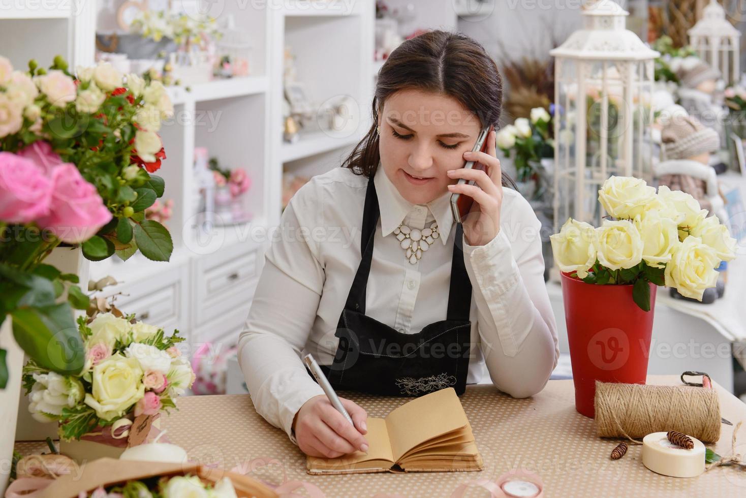 porträtt av leende blomsterhandlare som pratar i telefon foto