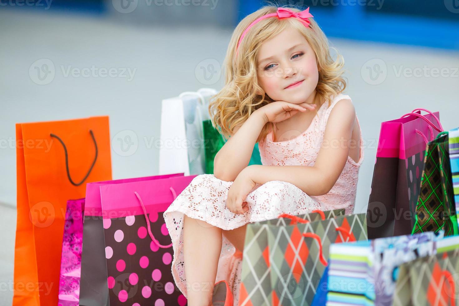 liten flicka med påsar går till butiken foto