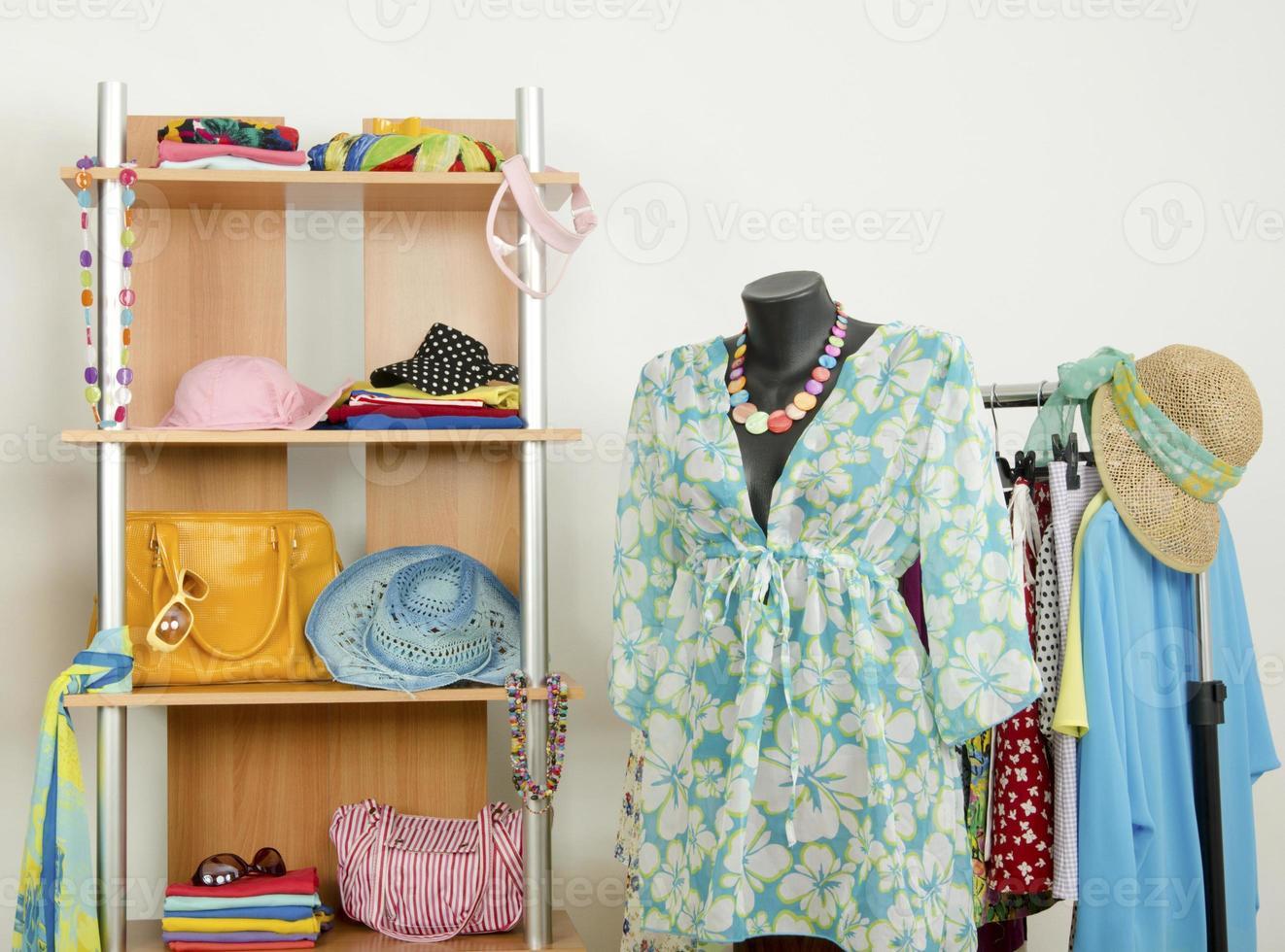 garderob med kläder och en stranddräkt på en skyltdocka. foto