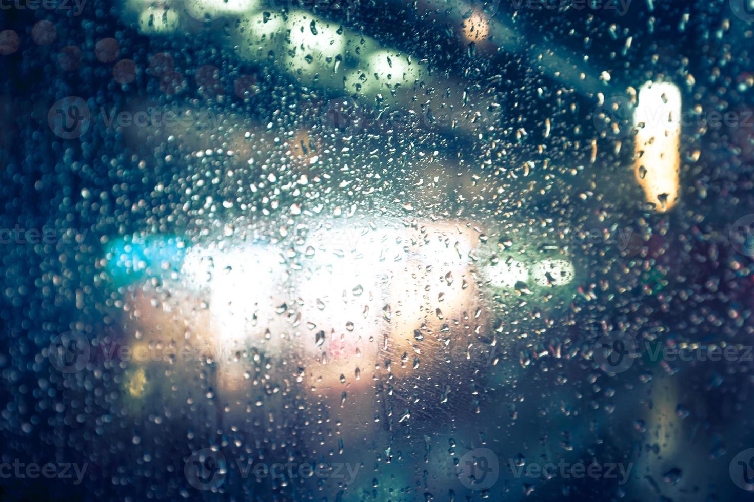 bokeh defocused bakgrund av staden regnar ljus och natt foto