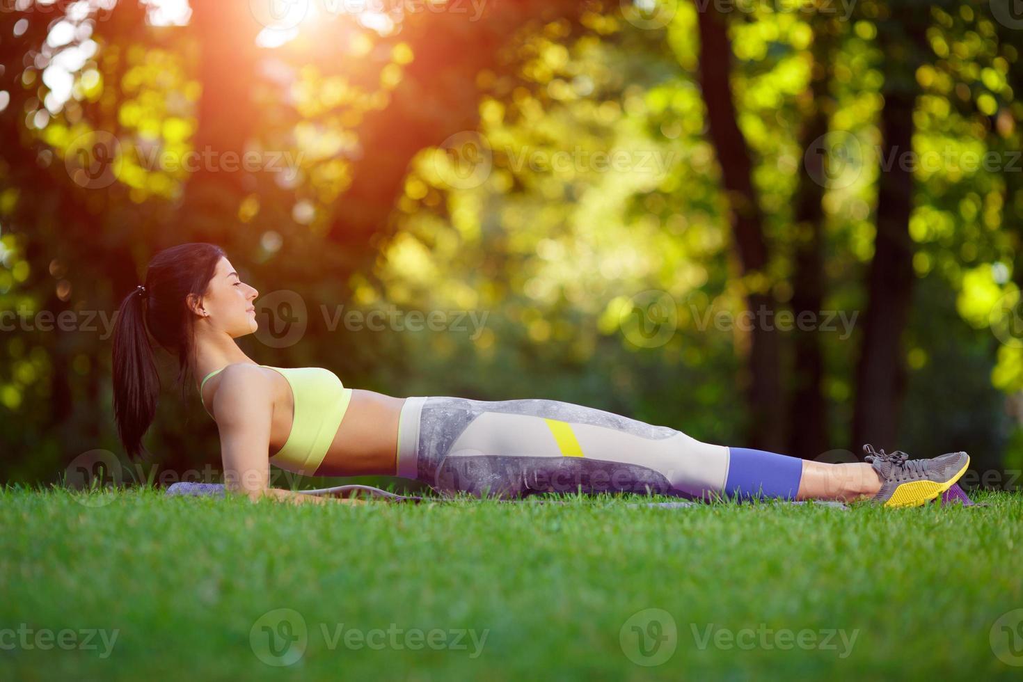 kvinna gör fitnessövningar i parken foto
