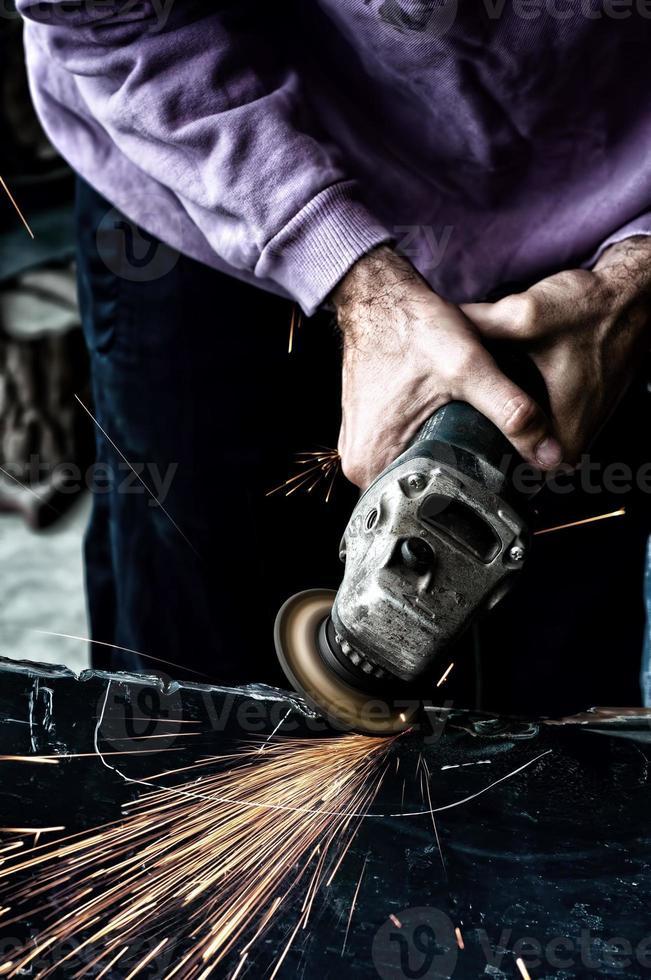 industriarbetare som använder en liten kvarn för skärning av metall foto