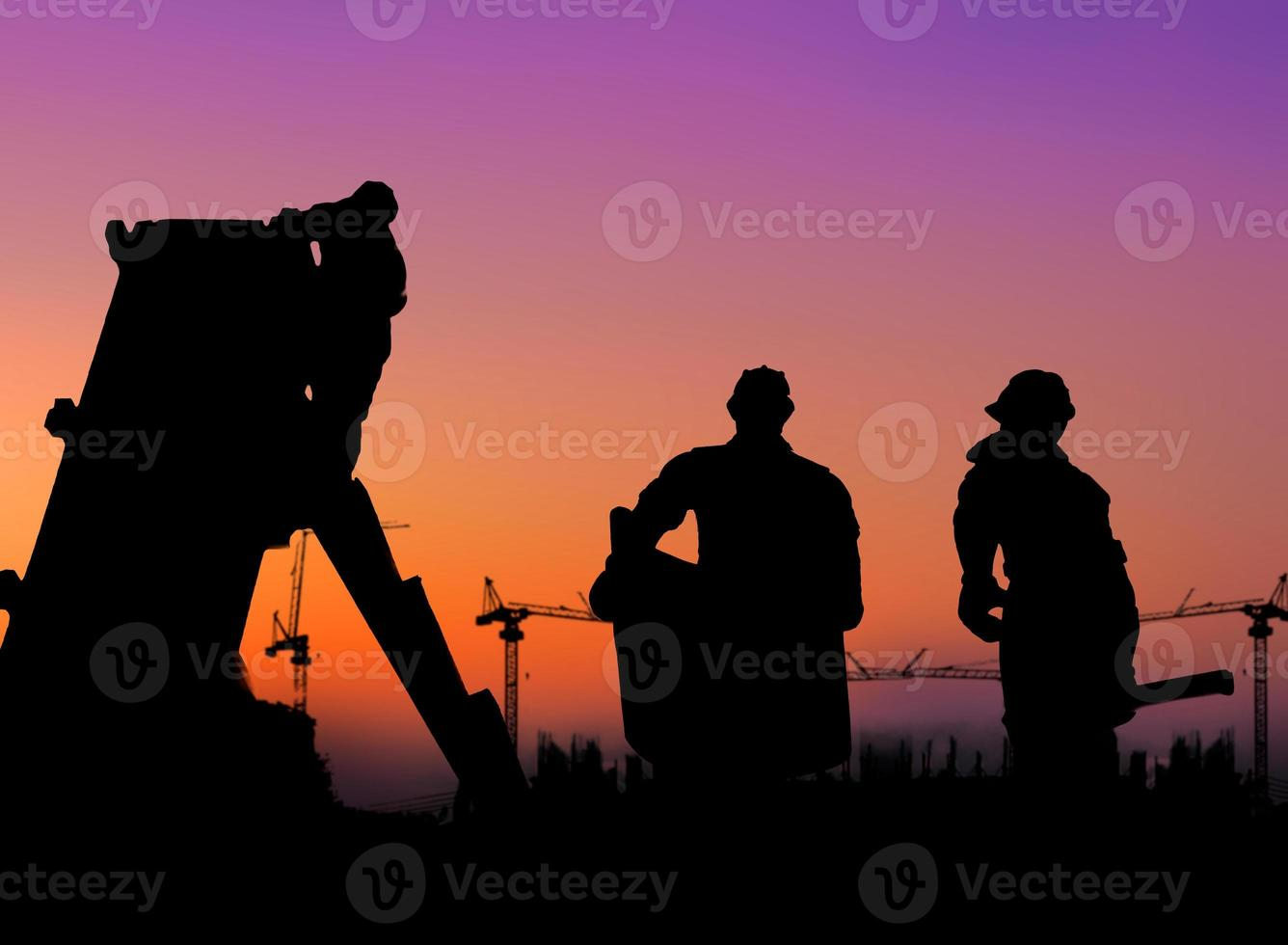 gruppen arbetare som arbetar över suddig byggarbetsplats. foto