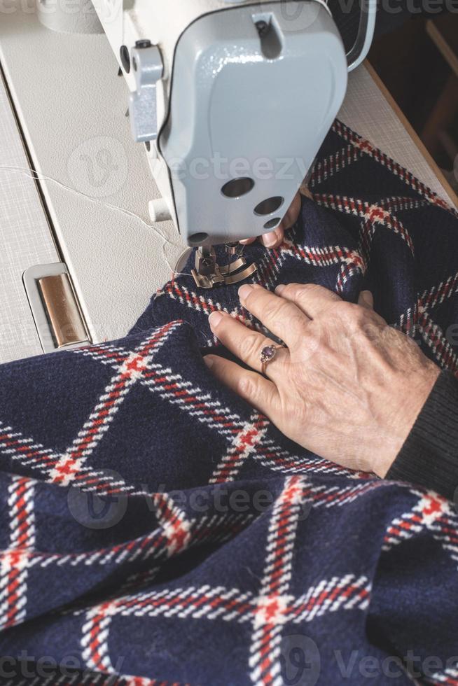 kvinna som sy på en symaskin. foto