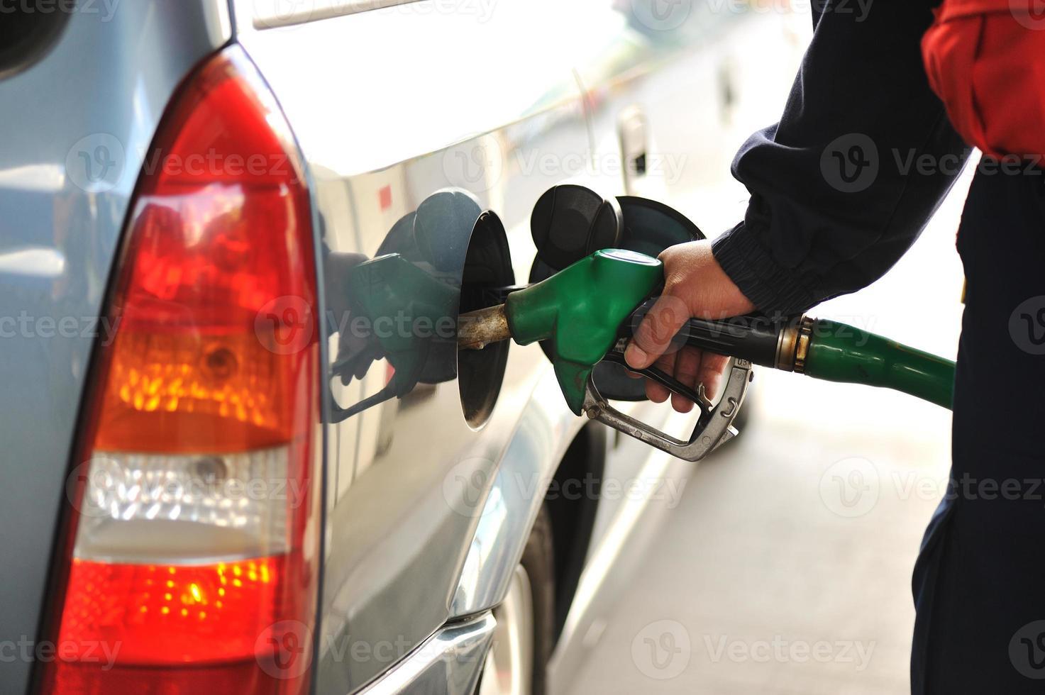 man påfyller bilen med bränsle på en tankstation foto
