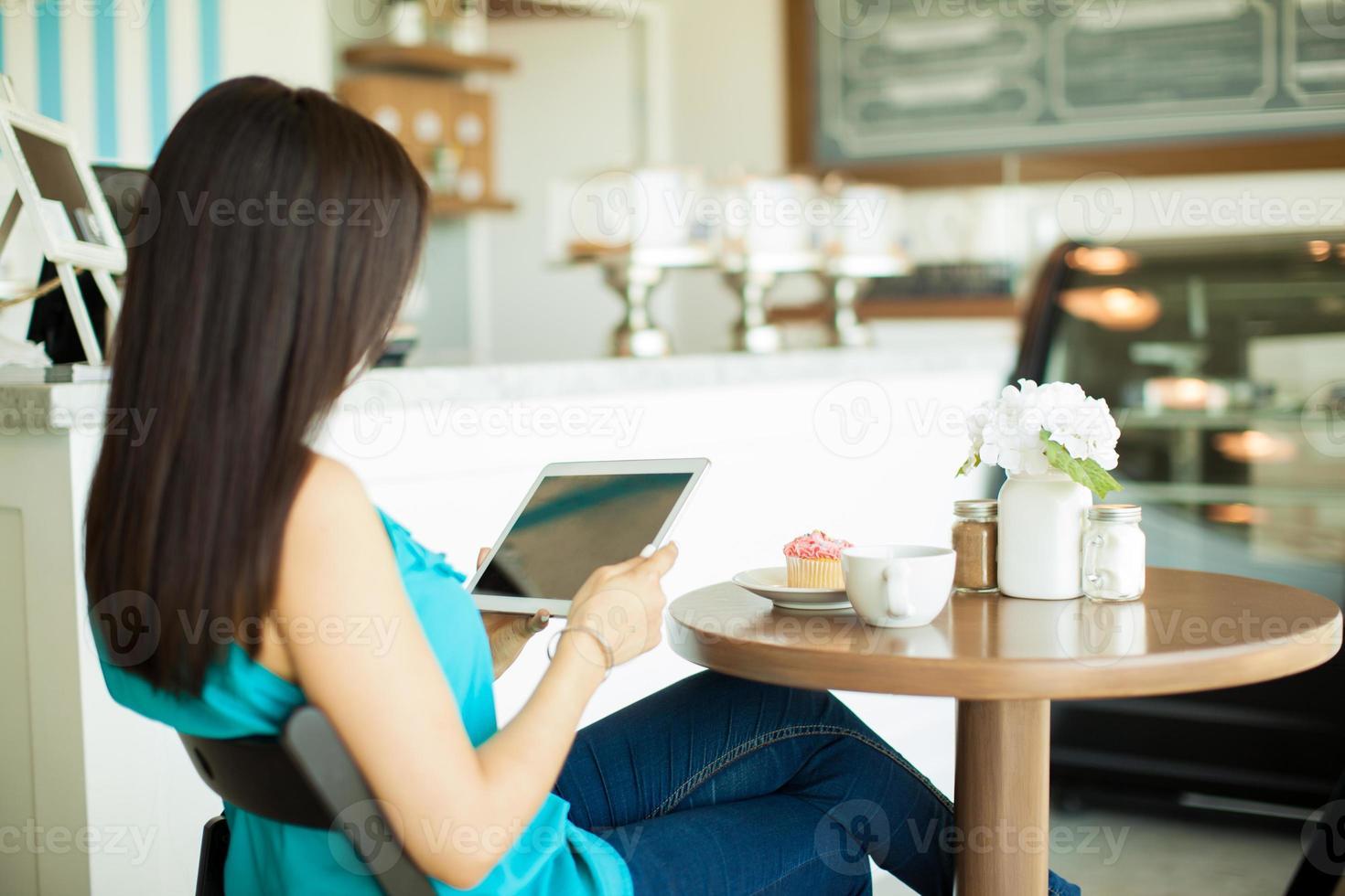 ung brunettläsning på ett kafé foto