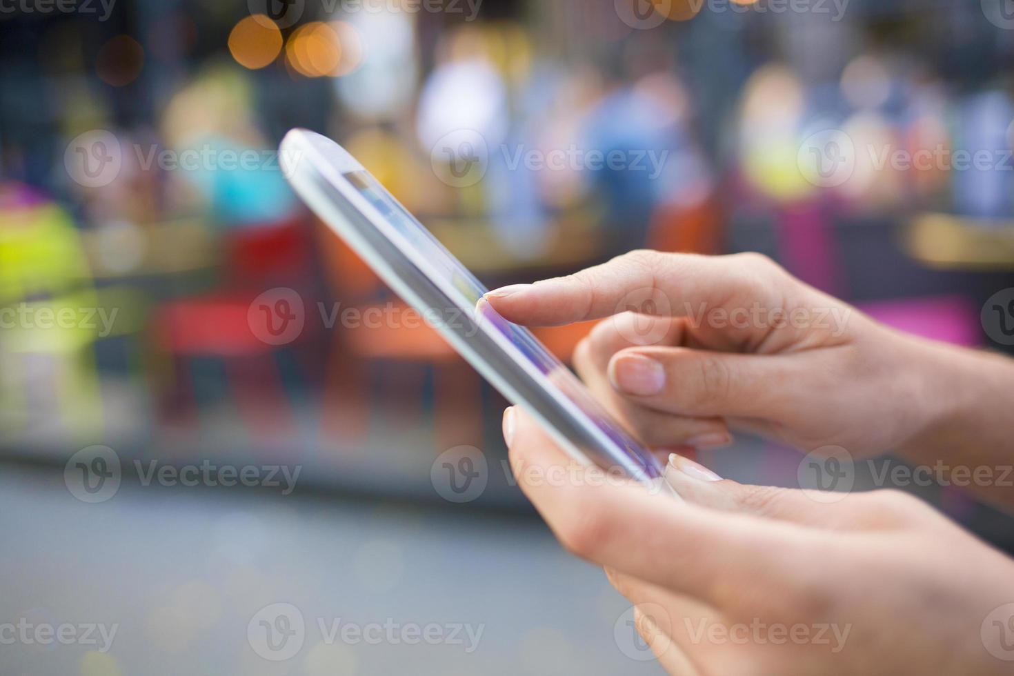 kvinna som använder mobiltelefon framför en caféterrass foto