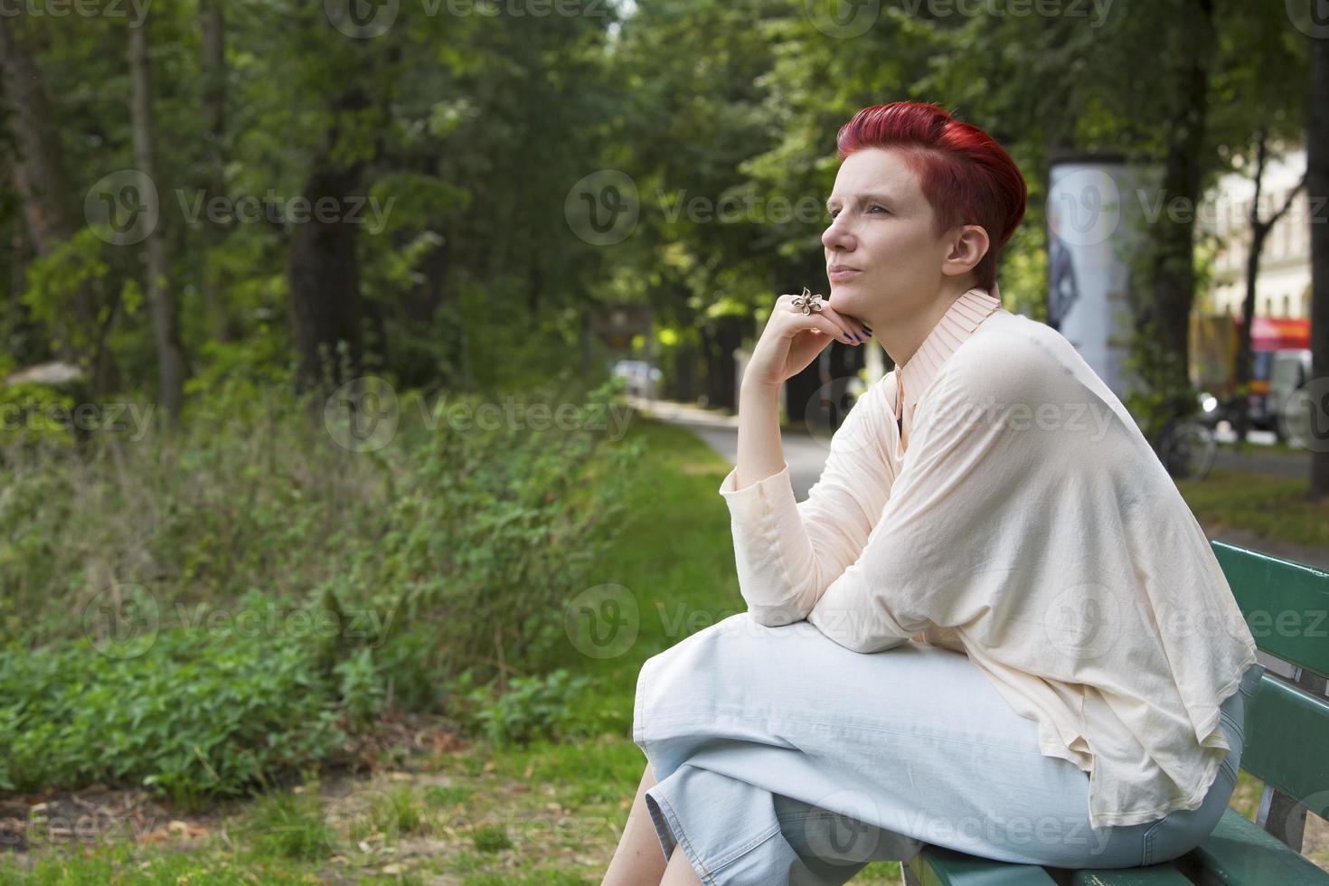 rödhårig sittande på en bänk foto