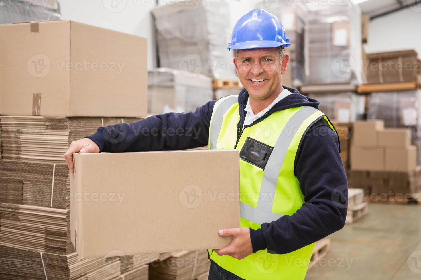 arbetare bär låda i lager foto