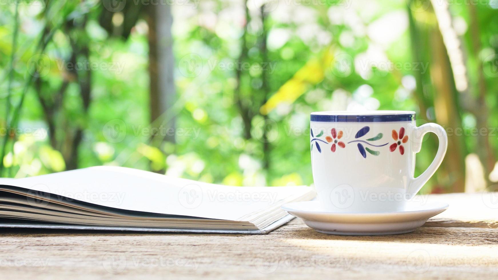 anteckningsbok och kaffekopp på träbord foto