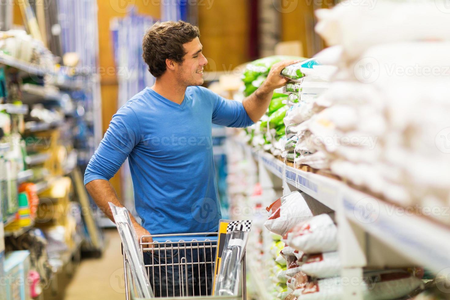 ung man shoppar i järnaffär foto