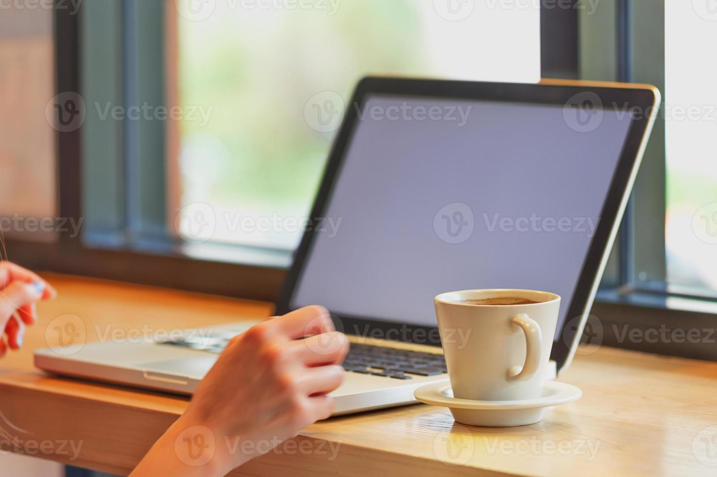 asien vacker med sin bärbara dator och dricka kaffe på café foto