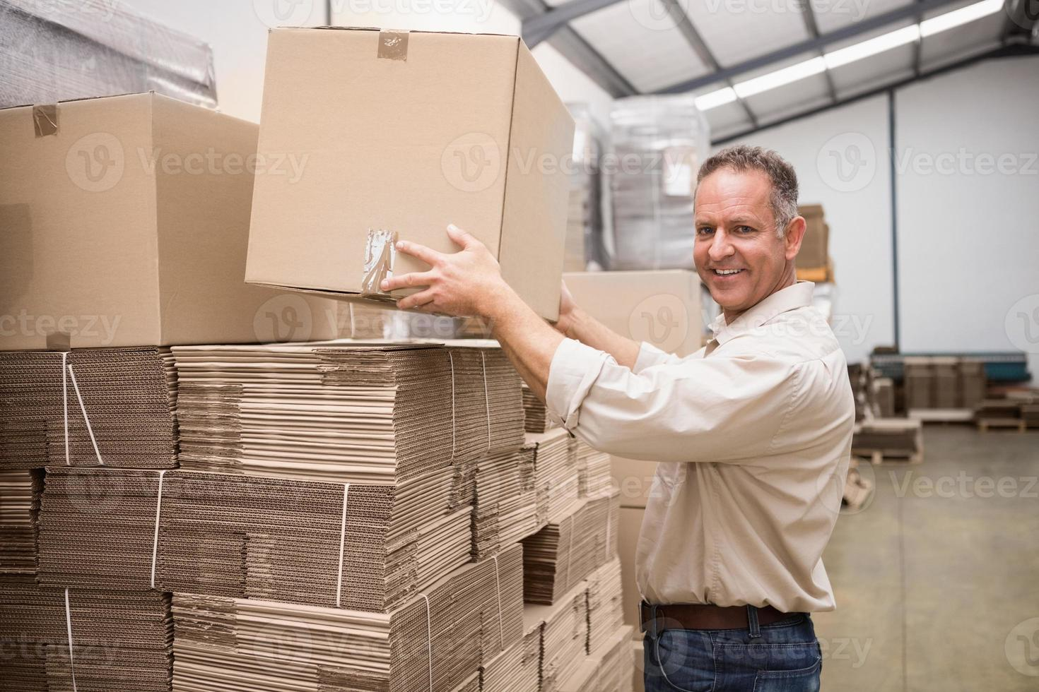 leende lagerarbetare tar en låda foto