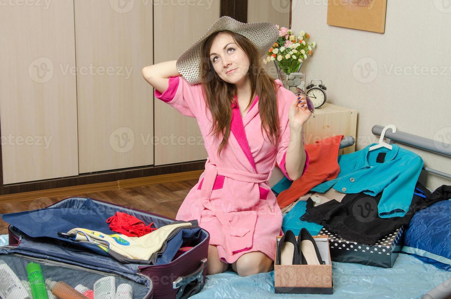 tjej drömmer om semester packa resväskor foto