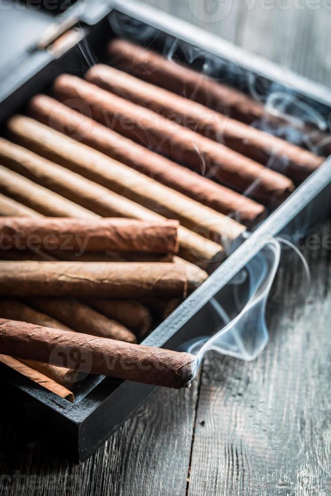 rök stiger från en brinnande cigarr på trähumidor foto