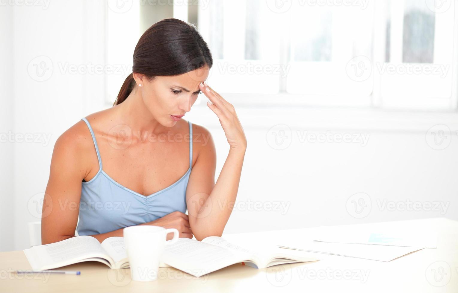 vacker kvinna som koncentrerar sig på att läsa böcker foto
