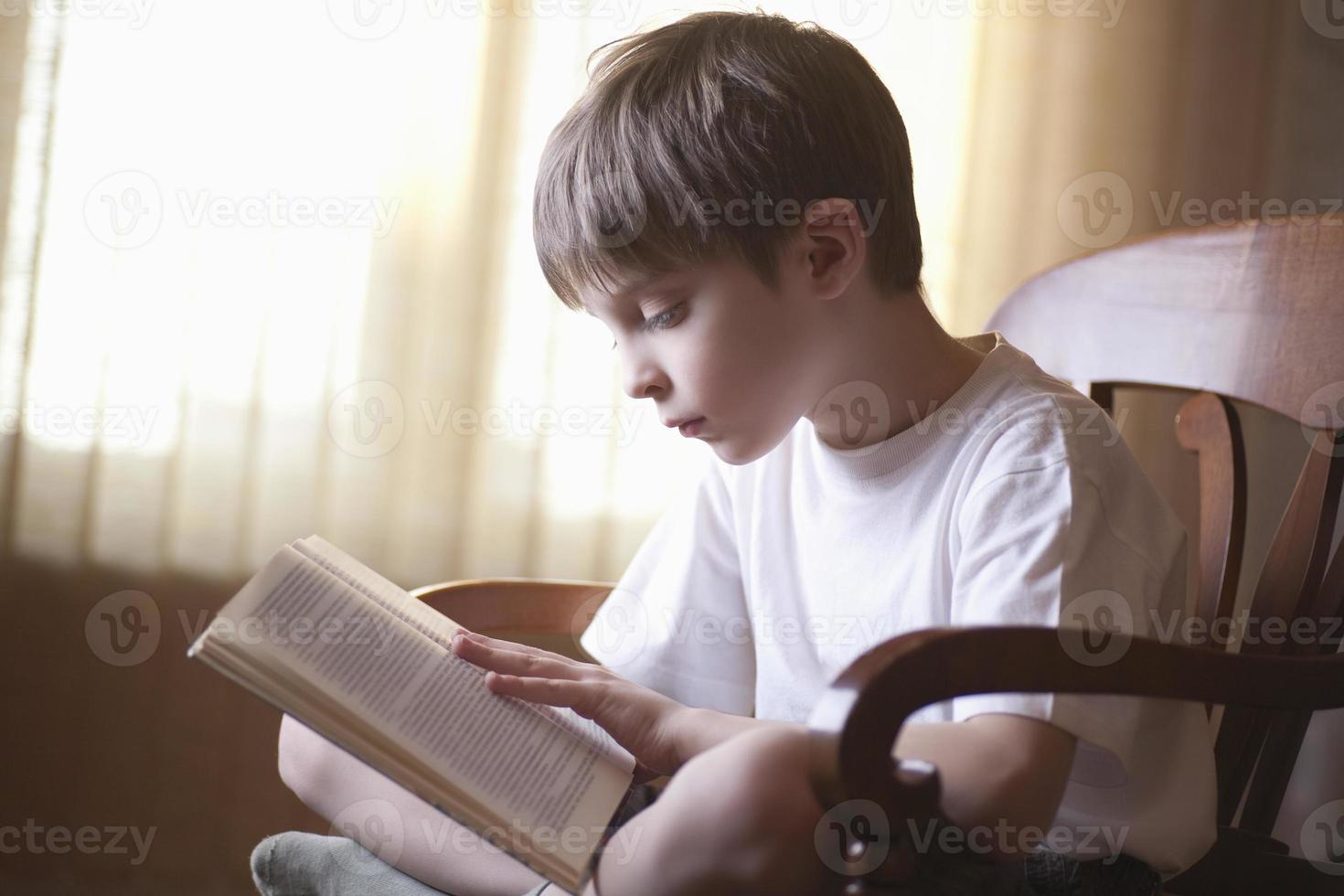 pojke läser bok på stol hemma foto